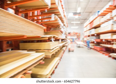 Blurred wooden bars from floor to ceiling at lumber yard of hardware store in America. Rack of pre-cut panel, mill timber, red oak, poplar, cedar, siding, plywood on flatbed cart. Customer shopping.