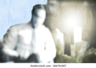 Blurred young businessman working in office. City skyline in the background.