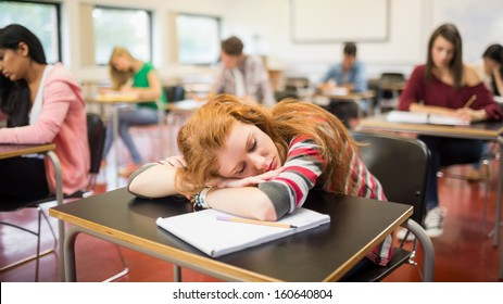 Blurred young college students sitting in the classroom with one asleep girl
