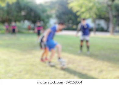 Blurred Young Football Players Running and Kicking Soccer Ball on a Soccer Pitch.