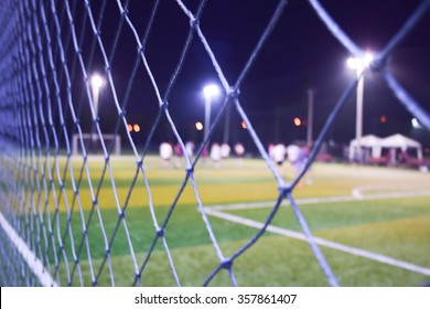 Blurred of young kids playing a youth soccer match outdoors on night time.