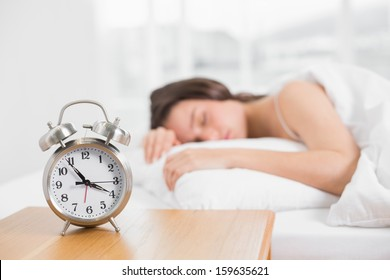 Blurred young woman sleeping in bed with alarm clock in foreground