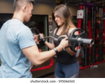 Blurred of young women doing biceps weight training with coach