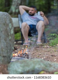 A blurried man is drinking as a background of a burning camp fire
