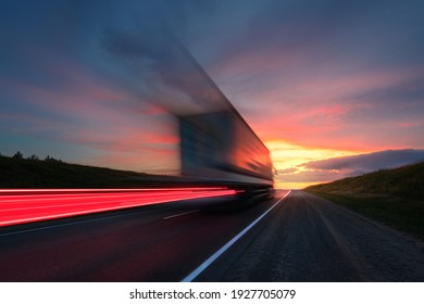 Blurring. A large truck is driving along the highway at high speed. Sky with bright red clouds. Delivery of cargo.
