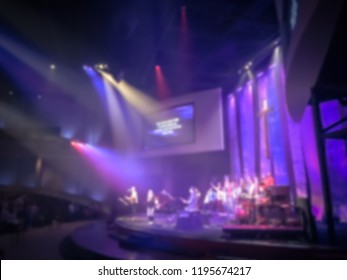 Blurry abstract worship band and the choir at Bible Church in Texas, USA. Dark background, smoke, concert spotlights for Christian concept. Worship lyric projection