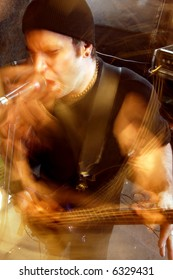 Blurry atmospheric abstract noisy hazy image of a bass player rippin' thru songs. Shot with slow shutter speed and flash for lots of movement and effect.