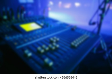 Blurry background of audio mixer for musician on stage.Pro sound mixing controller panel to mix music,voice and vocal.Bright stage lighting scene.Focus on controller knob,regulator