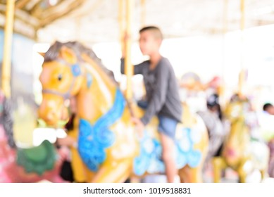 Blurry background of a boy ride carousel at the amusement park.Funny time for children.