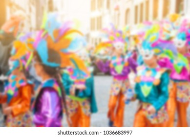 Blurry background carnival parade of the world, traditional festival present with people dance in mix colors costume and put white mask deco with feather, funny and happy national culture and musical.