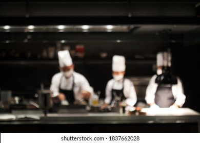 Blurry background of chef cooking food in kitchen bar in restaurant.