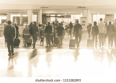 Blurry background family members walking with luggage along airport hallway terminal. Abstract blurred passengers or tourist travel with baggage. Bokeh morning backlit light