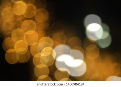 Blurry background image of defocused golden color abstract city street lights at night