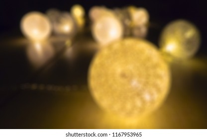 Blurry background with ligthen lampions on the table in the dark
