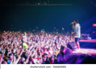 Blurry background of rap music concert in nightclub.Popular singer sings a song in microphone on scene of music hall.Entertainment event background.Dance floor crowd partying,view from stage