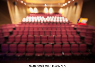 Blurry background of red seat in the theater without people.