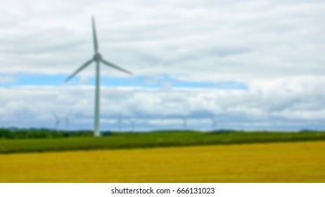 Blurry background of wind turbines, fields and sky