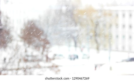 Blurry background of the winter. Slanting snow falling on blurred background. Urban landscape with snow falling in a city.
