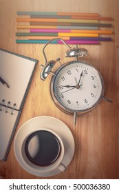 Blurry Black coffee Open notebook with pencil and old-fashioned alarm clock on wood table. with cross processing and split tone instargram like.Warm color and vintage moment.