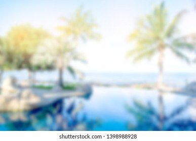 Blurry blackground morning time at swimming pool and the blue sea with palm,coconut trees with background white clouds and blue sky,  peacful and realax, tropical resort in asia.