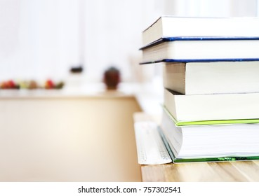 Blurry Book stack on wooden table and ruler with background of home office, Business or education background concept