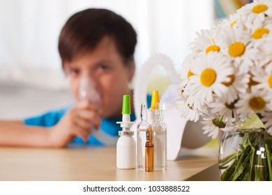 Blurry boy using inhaler device with medication in the foreground - allergy and asthma treatment concept