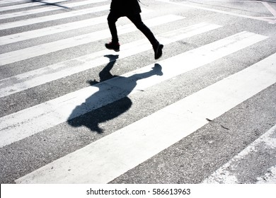 Blurry child's legs and kid's shadow with a backpack, on crossing while running over the street