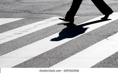 Blurry city street zebra crossing with one walking pedestrian legs silhouette  making  shadow in black and white high contrast