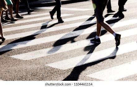 Blurry city zebra crossing with walking pedestrians legs making long shadows in black and white high contrast