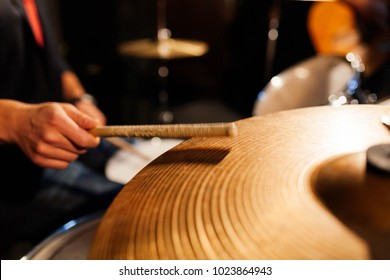 Blurry close-up  of a cymbal being hit by the the drummer of the band with a drum stick. Focus on the cymbals.