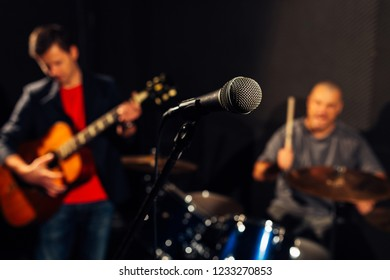 Blurry closeup of a microphone and two men playing the guitar and drums in the background. Focus on the microphone.