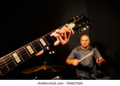 Blurry close-up picture of a guitar grif. Photo is focused on the guitarist's hand.