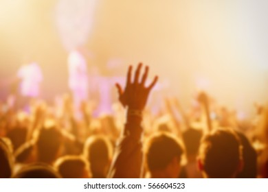 Blurry crowd of music fans enjoy show in nightclub.People put hands up to favorite musician.Excited fan wave hands.Dj music festival background