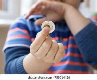 Blurry of Cute little boy holding one pound coin and looking at camera with smiling face, Happy boy wearing mismatched clothes with smiling face after got one pound for donation, Children development