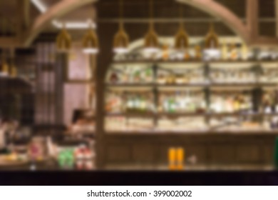 blurry defocused image of glasses and bottle of alcohol beverage on wooden counter bar