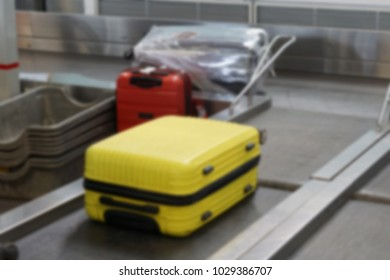 Blurry or defocused image of a luggage going into scanning conveyer in the airport.
