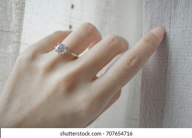 Blurry of diamond ring on woman's finger while touching the blinds. (soft and selective focus)