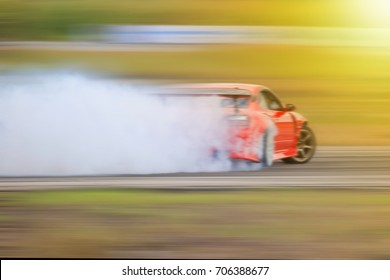 Blurry drift car motion spin rotating tire wheel with white smoke on the road