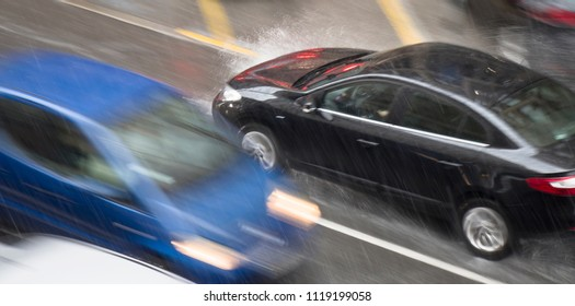 Blurry driving car in the street hit by the heavy rain with hail, in rainy spring season in motion blur panning shot from above