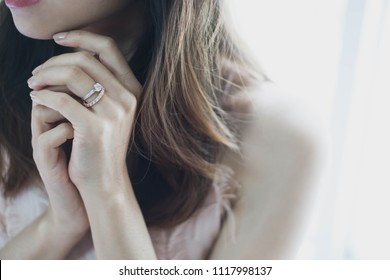 Blurry of elegant diamond ring on woman finger with window and sunlight tone background.Love and wedding concept.