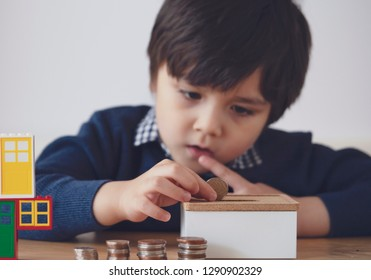 Blurry face of kid with thinking face putting 10 pence on money box, Selective focus little boy making stack British money coins and counting. Learning financial responsibility and saving for future