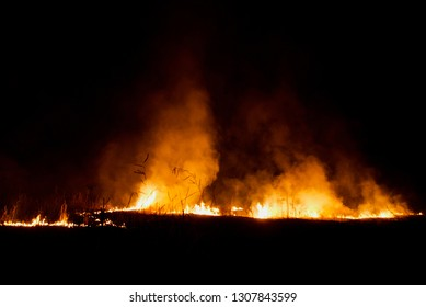Blurry fire flames with smoke around an urban area at night