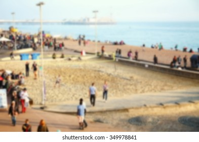 Blurry focus of beach scenery in england beach with a group of people playing beach volleybal represent the blurry background and people activity concept related idea.