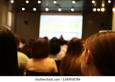 Blurry focus on peoples in conference room with projector screen, audience and speaker.
