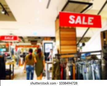 Blurry focus scene of shopping area while hanging sale signage scene.