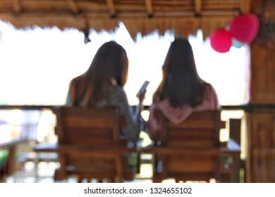 Blurry focus of two young lady on smartphones from behind.