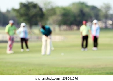 blurry golfers hit sweeping golf course in the summer on sunshine for relax time