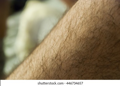 blurry hairy legs of man on bed in bedroom