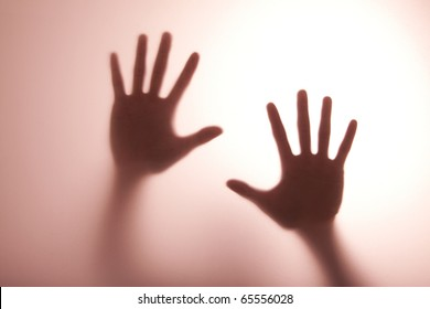 blurry hand reaching out and touching glass with Warm tone of light