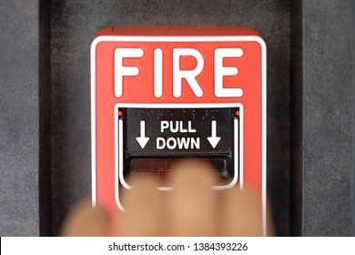 Blurry hand try to pull down for activate fire alarm system at the wall. The hand of man is pulling fire alarm on the wall. Concept warning and alert fire alarm building. Protection and emergency call